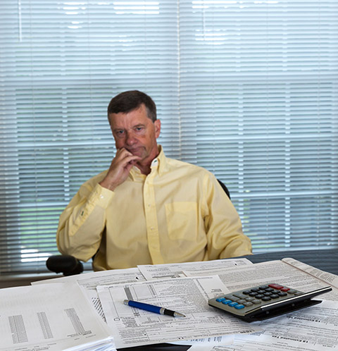 Senior caucasian man weary from preparing tax form 1040 for tax year 2012  with calculator